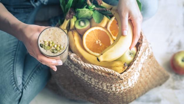 スムージーと果物を持つ女性