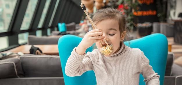 Очаровательная смешная девушка ест суши в ресторане