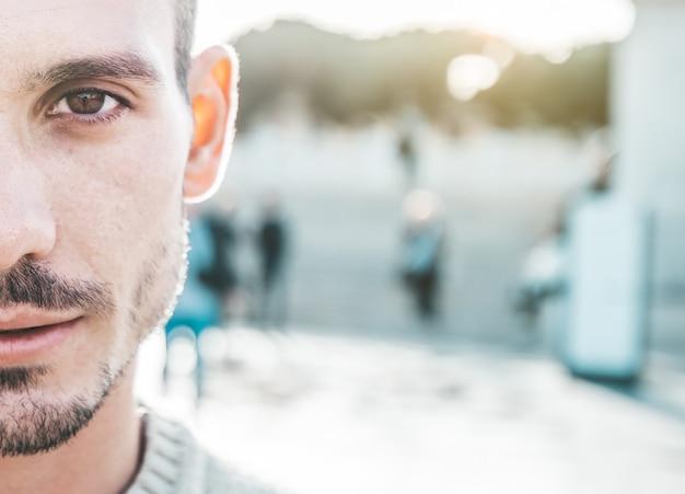 屋外のハンサムな若い白人男の肖像画をクローズアップ。半分の顔。