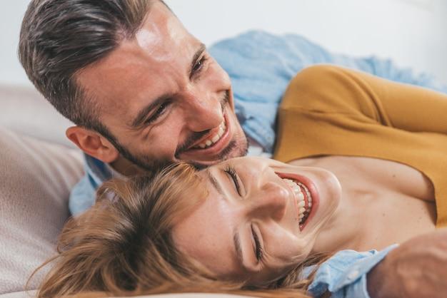 一緒にテレビを見て笑って楽しんで美しいロマンチックなカップル。一緒に過ごす家で愛の若者。