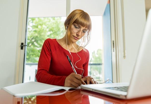 自宅のコンピューターで勉強して美しい若い女子学生。オンライン学校のコンセプト