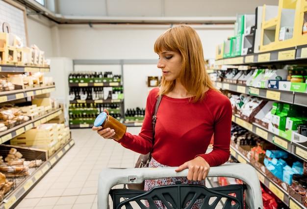 Женщина покупает еду в супермаркете.