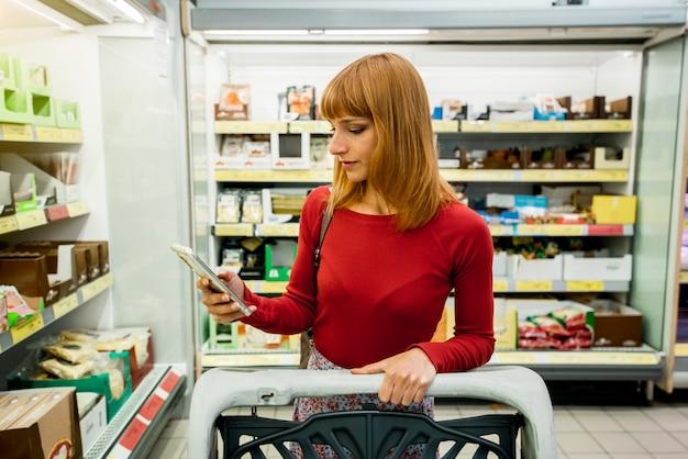 Женский клиентов с помощью мобильного телефона в супермаркете. женщина, покупки в продуктовом магазине.