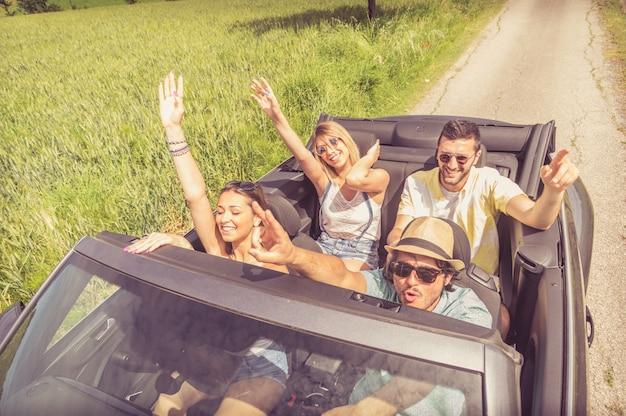 Группа друзей, с удовольствием на машине путешествие по европе. друзья на каникулах едут по дороге