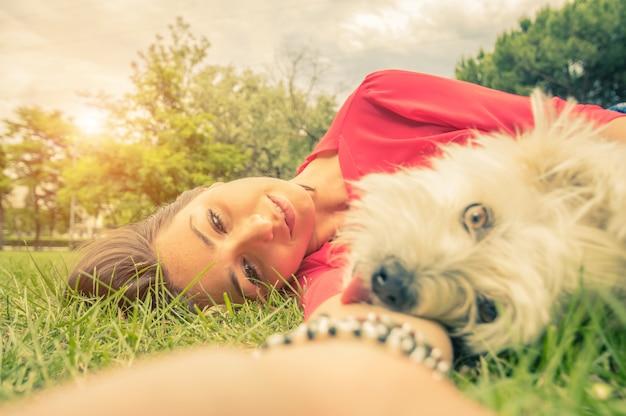 Молодая девушка, принимая селф с ее собакой, лежа на траве в парке