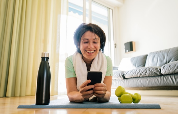 自宅でスマートフォンを使用して笑って幸せな年配の女性はフィットネストレーニングします。フィットネス、スポーツ、成熟した人々、テクノロジー