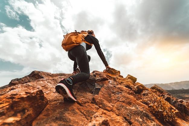 サンライズマウンテンピーク-バックパックを持つ若い女性が山の頂上にハイキング成功女性ハイカー。ディスカバリー旅行先のコンセプト