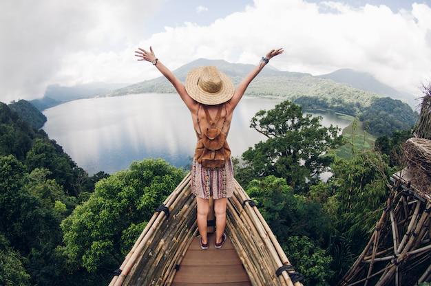 気楽に空中に腕を上げて崖の上に立っている幸せな女性ハイカー。アクティブな健康概念