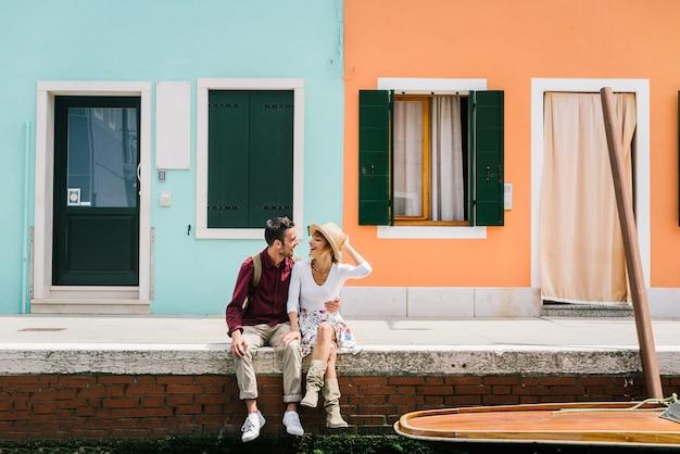 イタリア、ヴェネツィアの運河の上に座って休日を楽しんで愛の若いカップル。