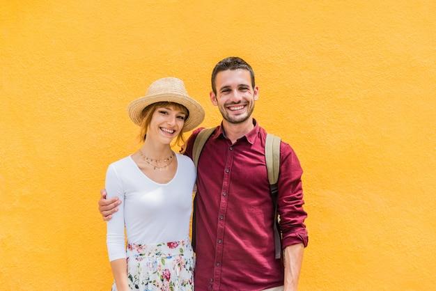 素敵なカップルが家族の肖像画、笑顔、嬉しそうに黄色の壁の背景にポーズします。