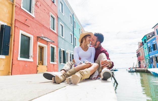 イタリアのヴェネツィアの運河の上に座ってキス恋のロマンチックなボーイフレンドとガールフレンド。市内の夏休みを楽しんでいる素敵な観光客。