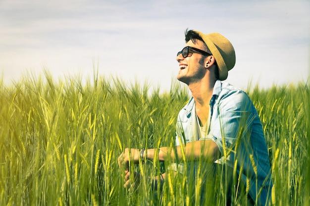 男は田舎-ライフスタイルコンセプトの草の上に座って笑う