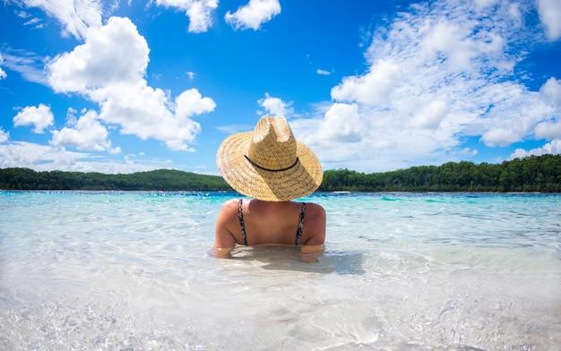 熱帯の青い水で夏にうれしそうなビーチを楽しんで幸せな女。