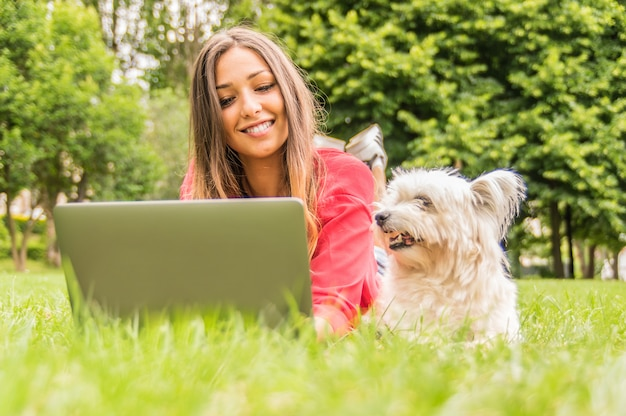 Собака смотрит на своего владельца с помощью пк. молодая привлекательная девушка изучает лежа в парке со своей собакой. понятие о собаке, людях, природе и технологиях