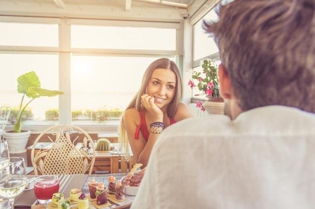 レストランでデートする幸せなカップル。彼女のボーイフレンドとの会話を持つ愛の女性