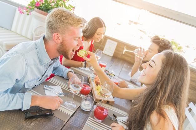 レストランで楽しんで幸せな親友。食べ物と遊ぶ素敵なカップル