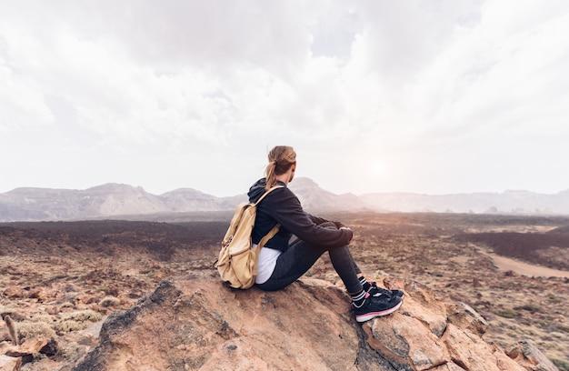 サンバレーを見ている山に一人で座っている女性。