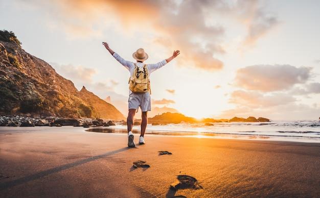 若い男が自由と人生を楽しんでいる日の出で海に広げられた腕、人々は幸福の概念を旅行します。
