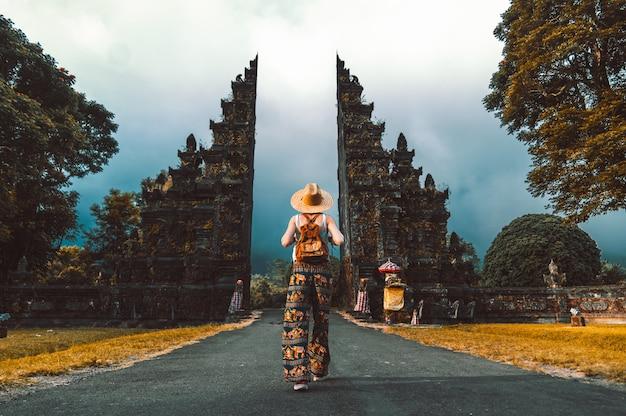 インドネシアのバリ島のヒンズー教の寺院を歩く休暇でバックパックを持つ観光女性