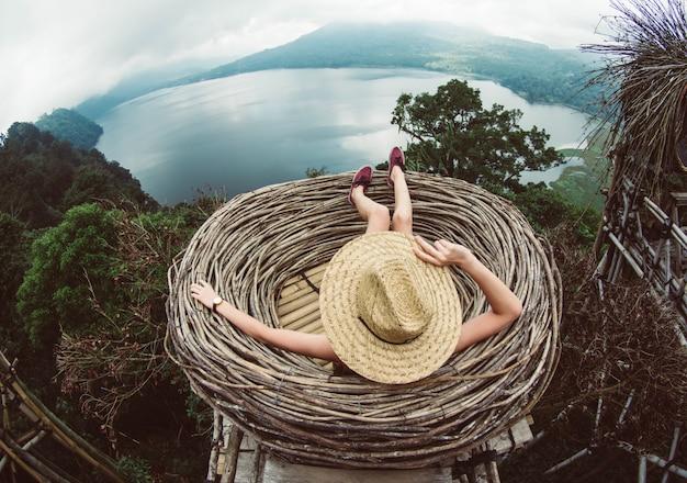 素晴らしい風景を見ている丘の上に座っている女性。アジアを旅する少女