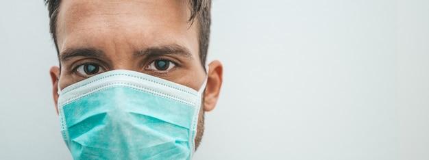 医療マスクを身に着けている孤立した男。コロナウイルスの概念