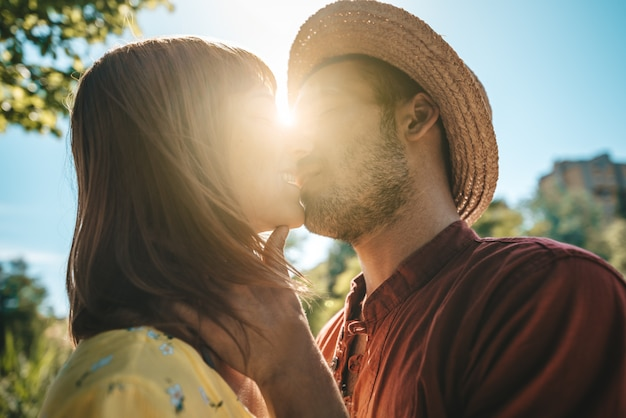 ロマンチックなカップルは屋外日没でキスします。