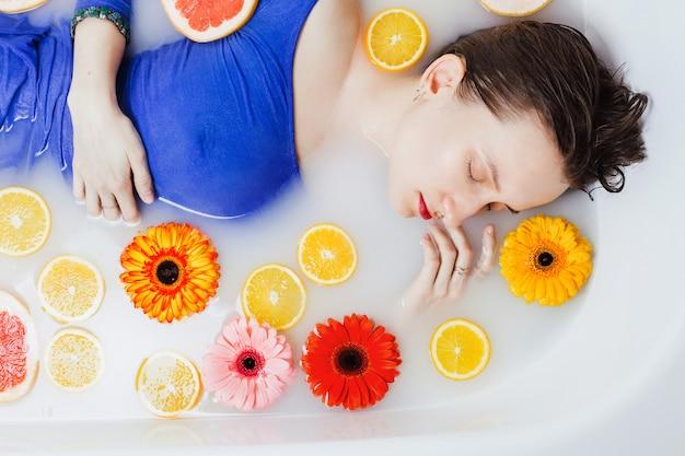 На снимке женщины в синем платье лежали в ванне с белой водой с цветами и цитрусовыми