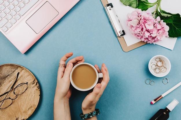ピンクのラップトップ、段ボール、オルテンシア、メガネ、その他のアクセサリーを備えた女性のワークデスクの美しいフラットレイアレンジメント。フェミニンなビジネスモックアップ