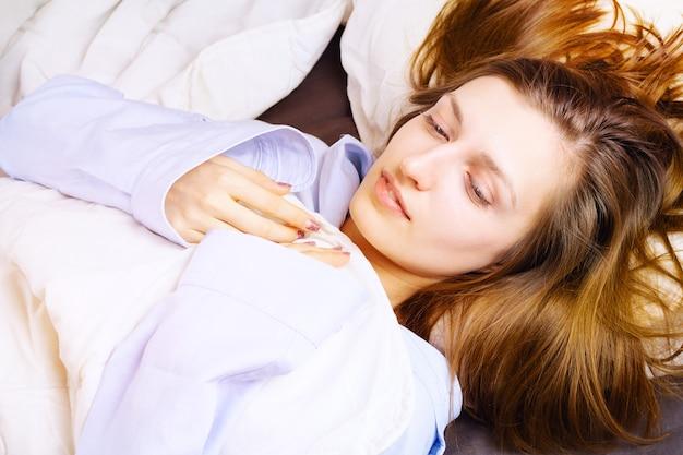ベッドで横になっている青いパジャマの若い笑顔の女性。朝のコンセプトです。 。