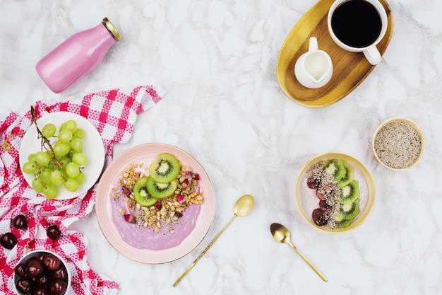 Вегетарианский завтрак с растительными мисками для йогурта, покрытыми ломтиками киви, мюсли, семенами чиа, бутылкой смузи и кофе с соевым молоком на мраморном фоне