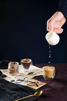 Крупным планом мужской руки лить растительное молоко в чашку кофе на столе с старинные заметки, полотенце, очки, ложку и банку с сахаром, селективный фокус