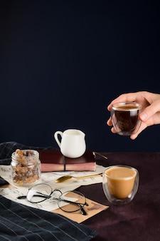 Макрофотография двух кофе, молоко держателя, банка с сахаром, очки и женщины рука держа чашку с эспрессо, селективный фокус