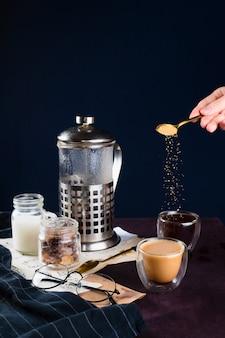 Макрофотография две чашки кофе, французская пресса, очки и женщины ручной заливки тростникового сахара, селективный фокус