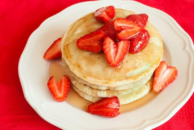 イチゴと赤の背景にシロップのパンケーキ。セレクティブフォーカス。