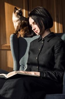 椅子に座っていると彼女の後ろに彼女の猫と本を読んで若い大人の女性の肖像画