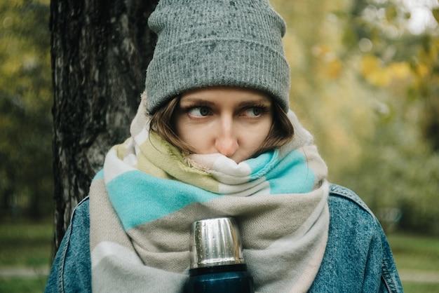 青い魔法瓶を屋外に保持しているセーターとデニムジャケットの若い大人の女性のライフスタイルの肖像画