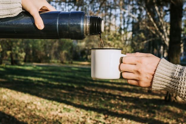 金属のカップと魔法瓶を押しながら屋外のセレクティブフォーカスの森の中でお茶を注ぐ女と男の手のクローズアップ