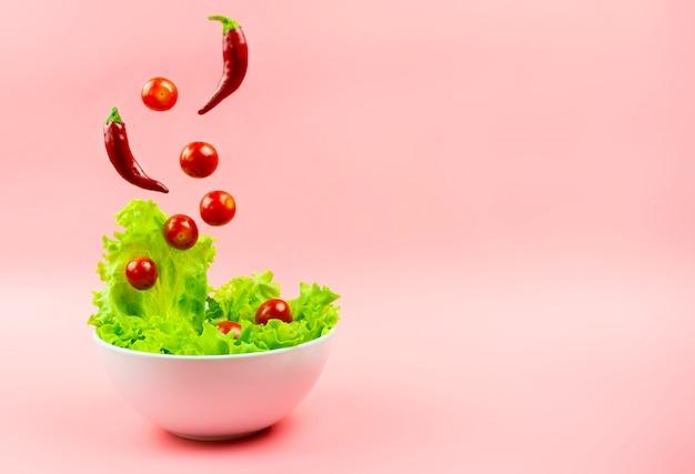 ピンクの白いボウルから飛び出すサラダ、チェリートマト、唐辛子。