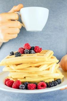 果実と一杯のコーヒーとワッフルを保持している人間の手のクローズアップ。ベッドでの朝食の概念。セレクティブフォーカス。