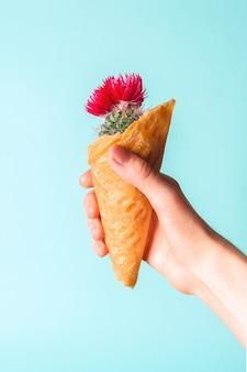 Крупный план вафельного конуса мороженого с кактусом внутрь в руке женщины. выборочный фокус