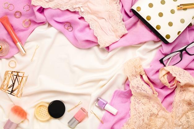 ランジェリー、化粧品、ジュエリー、その他のアクセサリーを備えた美しいフェミニンなフラットレイフレームアレンジ。上面図。