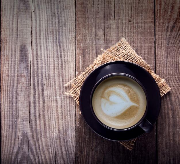 古いビンテージ木製テーブルの上のカプチーノコーヒーカップ