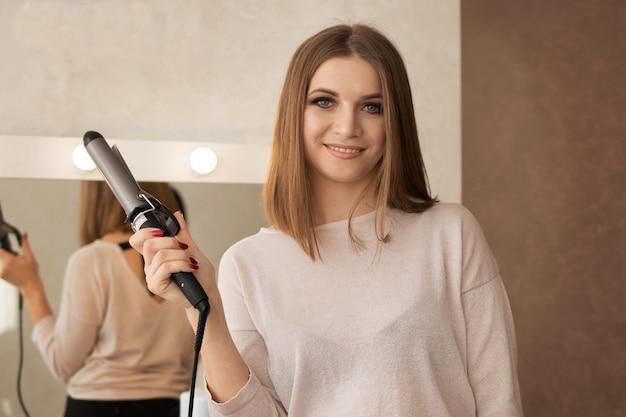 髪をねじるための平らな作業ツールと髪型女性のマスター