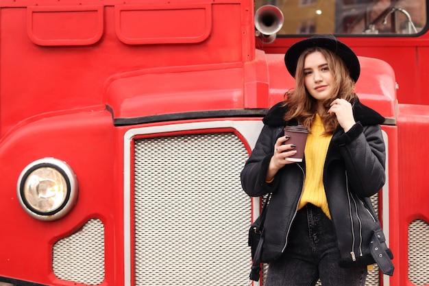 Молодая женщина в теплой стильной одежде гуляет по городу весной