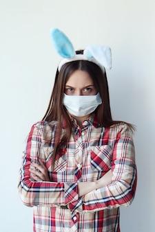 Молодая недовольная женщина в ушах зайчика и защитной маске