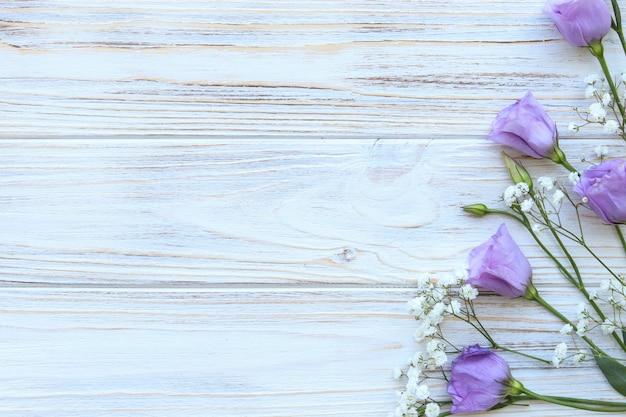 Фиолетовые цветы эустомы на белом фоне деревянные