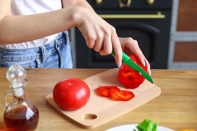 Женщина делает овощной салат, женские руки режут болгарский перец