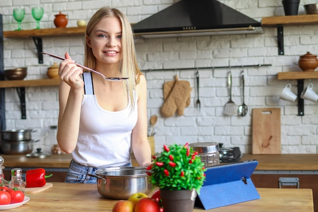 若いブロンドの女性は夕食を準備し、女性は調理済み食品を味わう