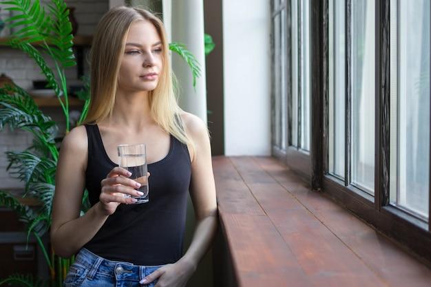 ガラスの水を持った女性が窓の外をよく見る