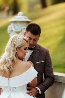 春の自然の屋外歩行の日の結婚式で新郎新婦。ブライダルカップル、幸せな新婚女と緑豊かな公園を受け入れる男。屋外の結婚式のカップルを愛しています。